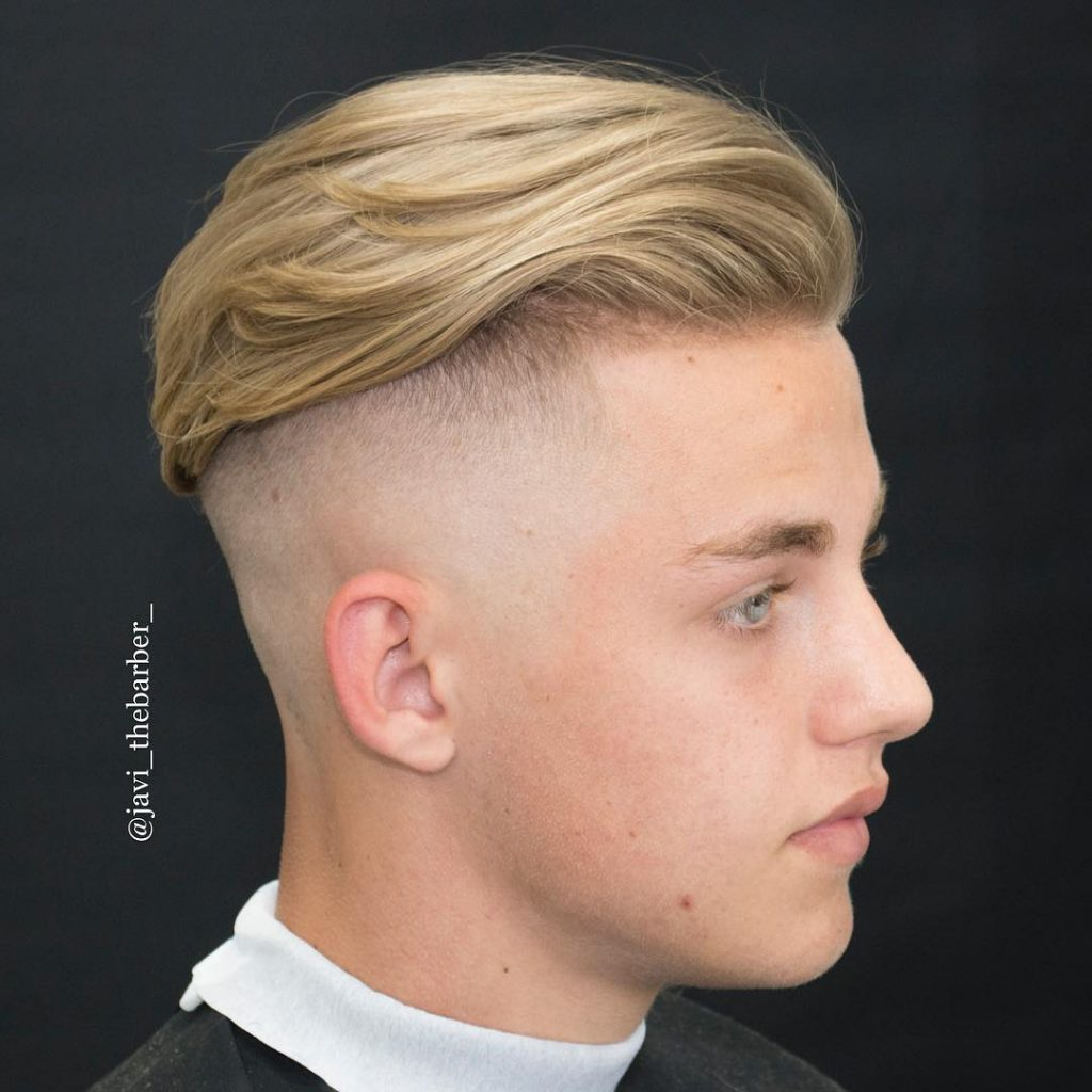 Longer wavy hair styled back undercut for men with high bald fade
