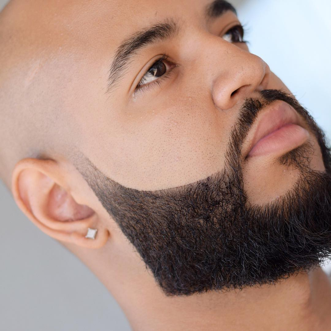 Bald head with thick groomed beard style