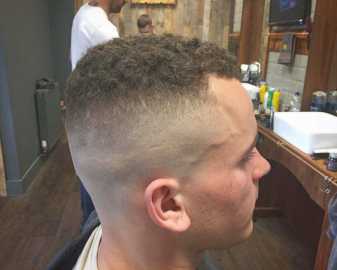 Curly hair high and tight with a bald fade