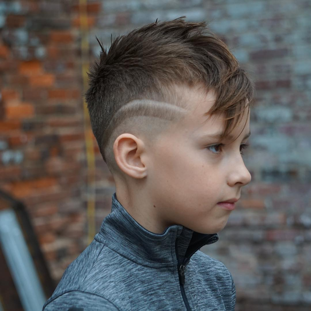 Mohawk haircut with long fringe and mid fade with hair design