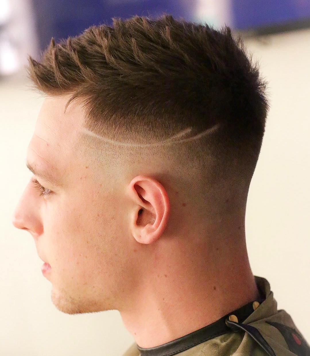 Short spiky mens haircut with mid fade and line hair design on sides