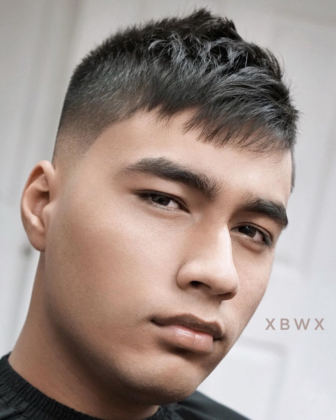 Short messy crop haircut for men with a high fade